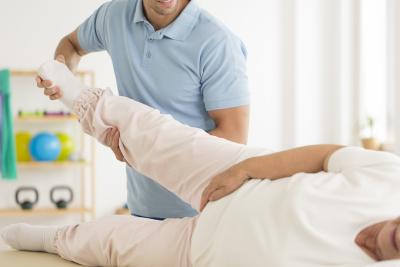 therapist rehabilitating senior woman`s joints