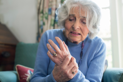 unhappy senior woman at home suffering with arthritis