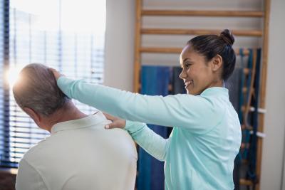 female therapist examining the neck of a senior man